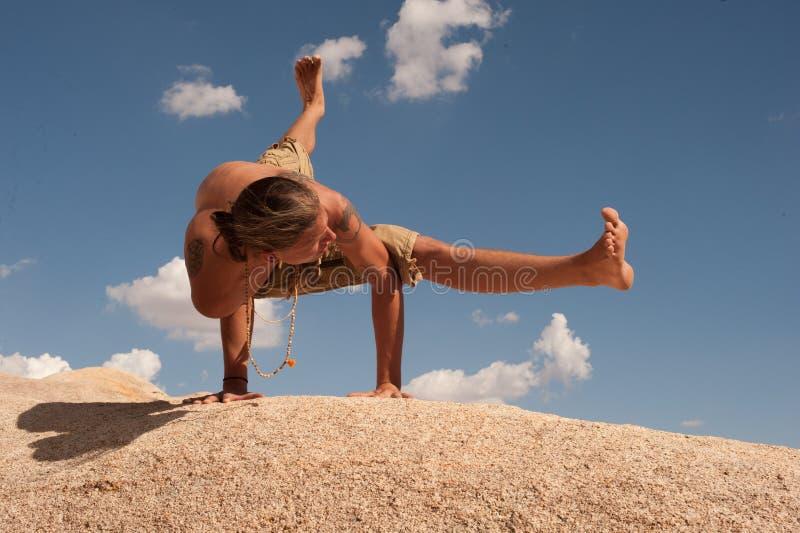Homem da ioga do deserto que equilibra em Eka Pada Koundinyasana foto de stock royalty free