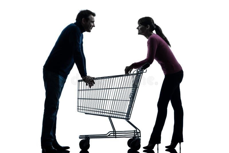 Homem da mulher dos pares com o carrinho de compras que data a silhueta flertando foto de stock royalty free