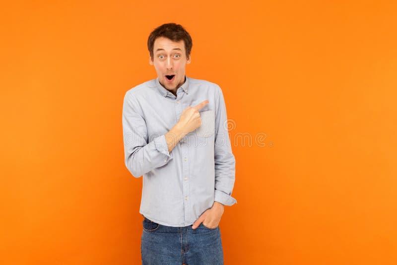 Homem da perplexidade que aponta o dedo no espaço da cópia, na boca aberta e no olhar fotografia de stock royalty free