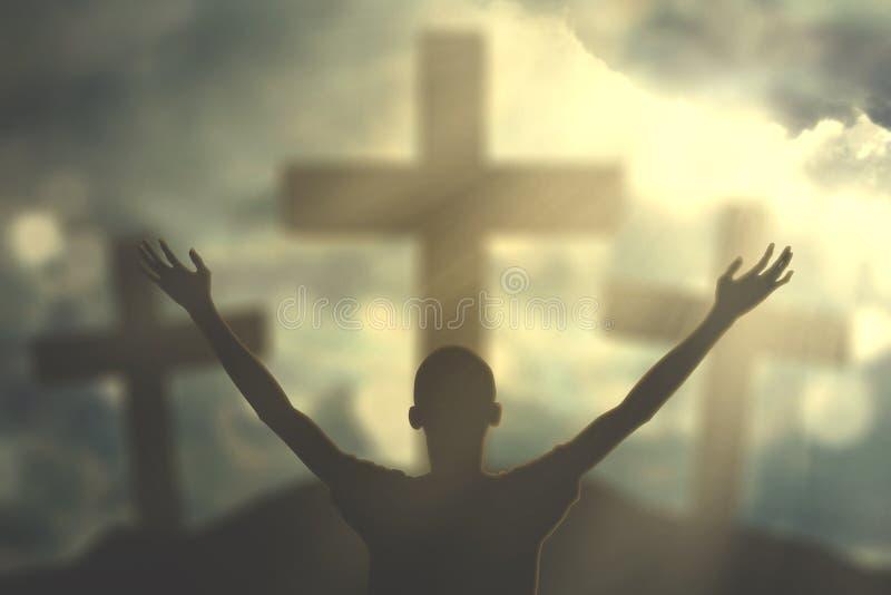 Homem da silhueta com símbolo do crucifixo fotografia de stock