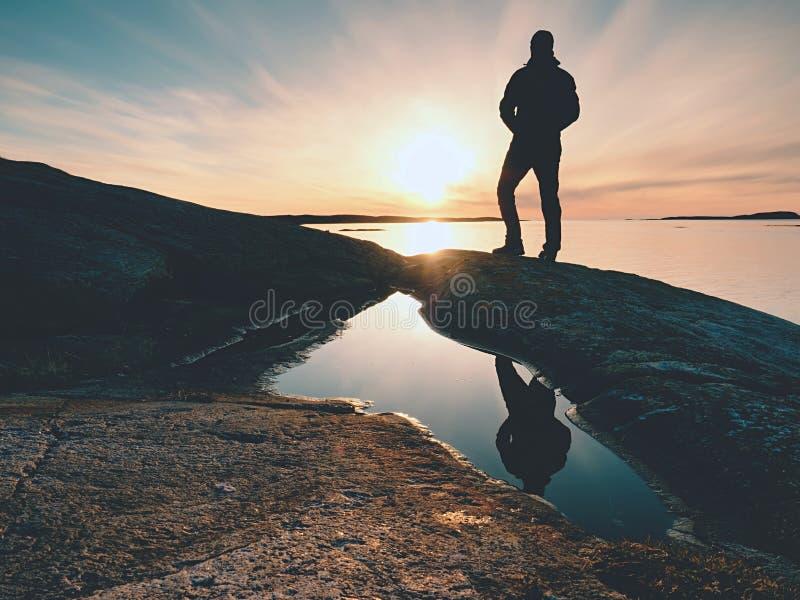 Homem da silhueta no penhasco acima do mar Suporte do turista apenas no horizonte de mar da rocha e do relógio imagem de stock royalty free