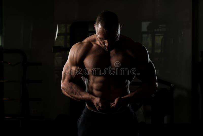 Homem dado forma aptidão do músculo que levanta no Gym escuro fotos de stock
