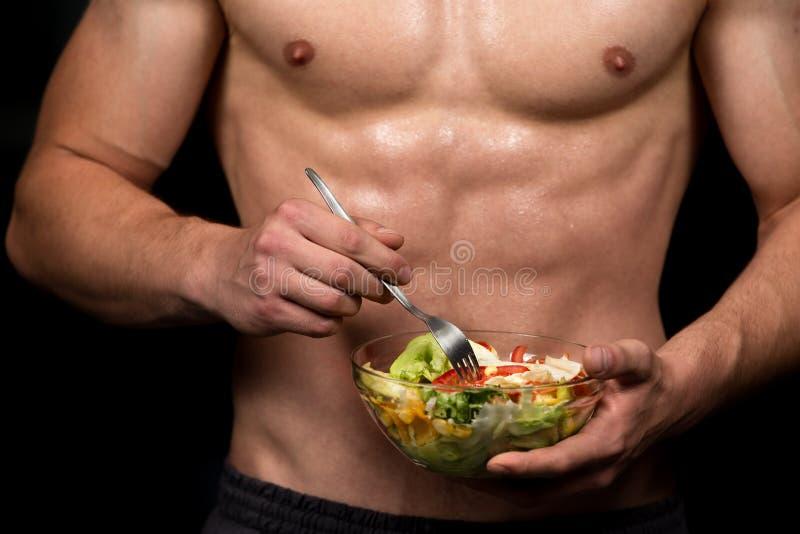 Homem dado forma e saudável do body building que guarda uma bacia de salada fresca, abdominal dado forma imagem de stock royalty free