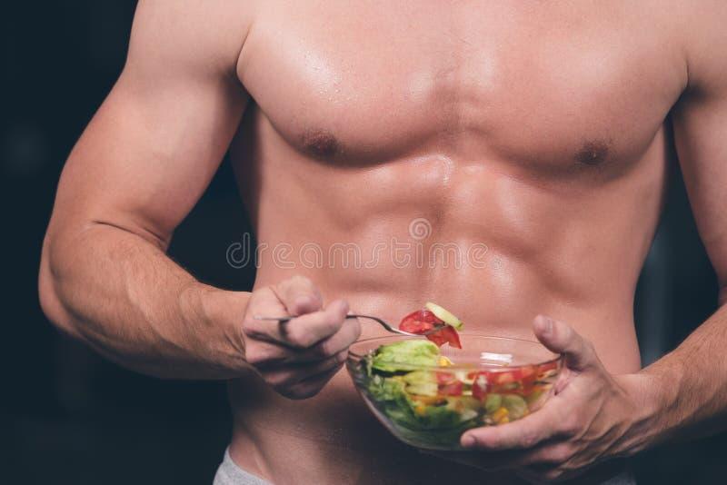 Homem dado forma e saudável do body building que guarda uma bacia de salada fresca, abdominal dado forma fotografia de stock