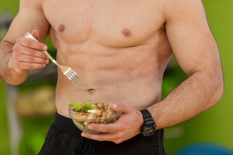 Homem dado forma e saudável do body building que guarda uma bacia de salada fresca, abdominal dado forma foto de stock