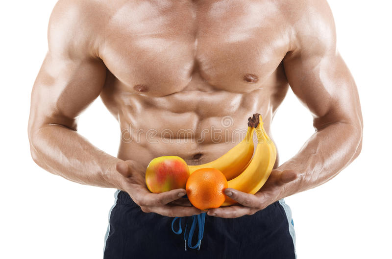 Homem dado forma e saudável do corpo guardando os frutos frescos, abdominal dado forma, isolados no fundo branco imagem de stock royalty free