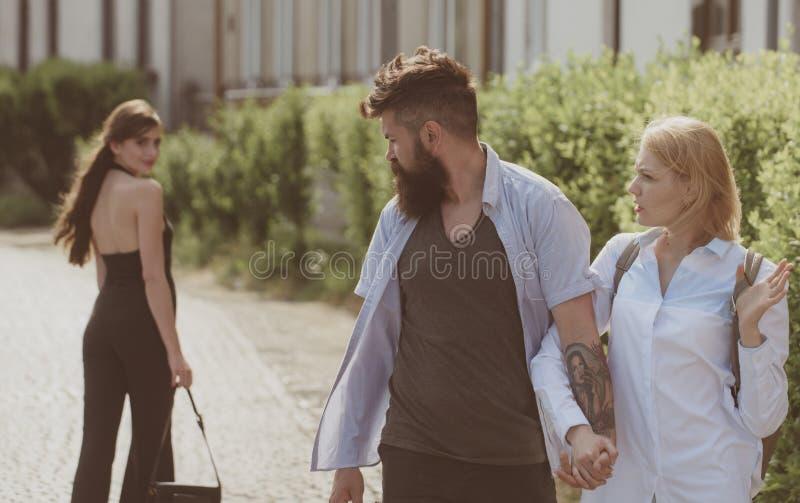 Homem das senhoras Homem farpado que olha a outra menina Moderno que escolhe entre duas mulheres Triângulo amoroso e threesome Ho imagens de stock
