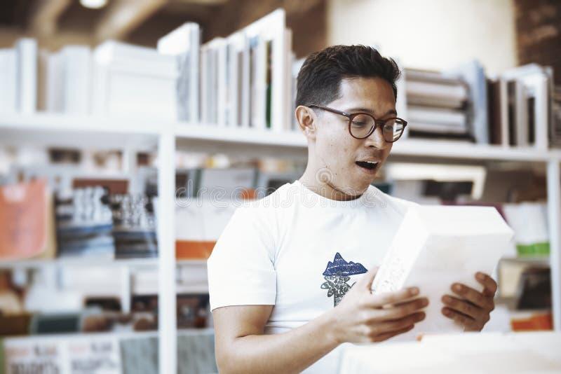 Homem de óculos atrativo novo que guarda o livro e que demonstra a cara surpreendida imagens de stock