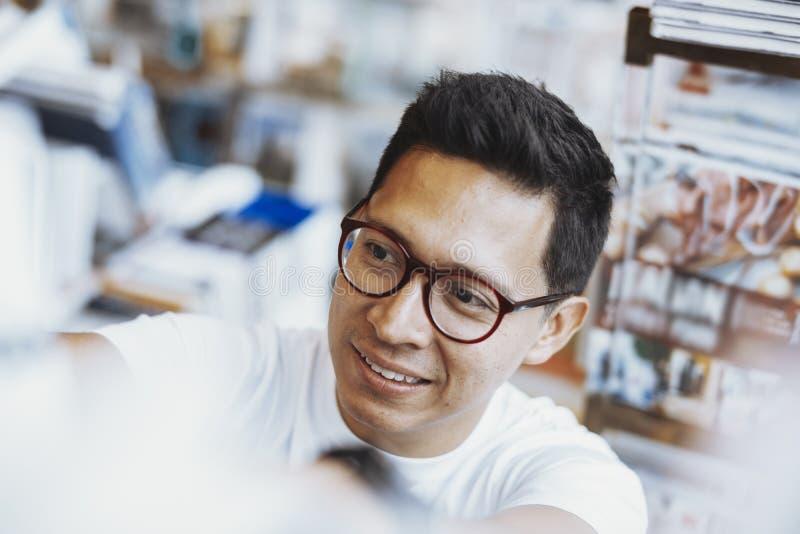 Homem de óculos atrractive novo que escolhe o livro em uma biblioteca fotografia de stock royalty free