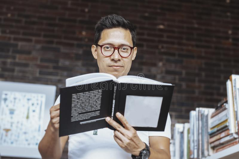 Homem de óculos novo que guarda o livro em umas livrarias fotografia de stock royalty free