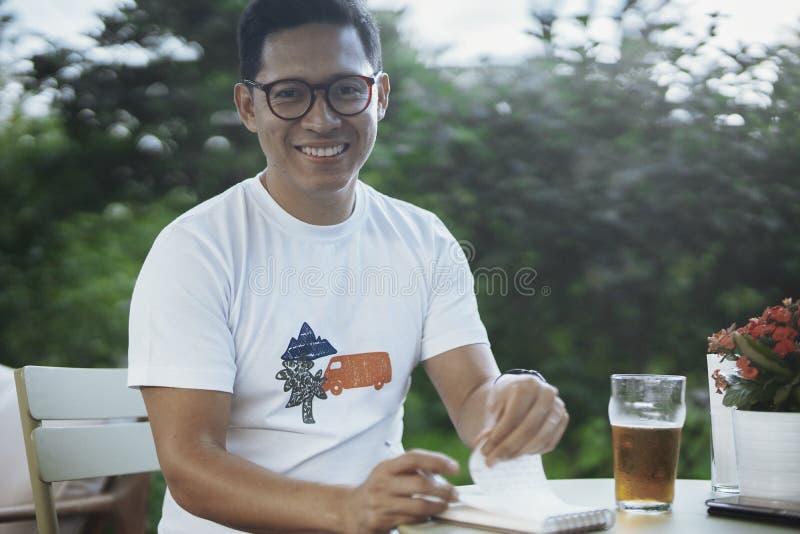 Homem de óculos novo que rasga para fora páginas do caderno fotografia de stock