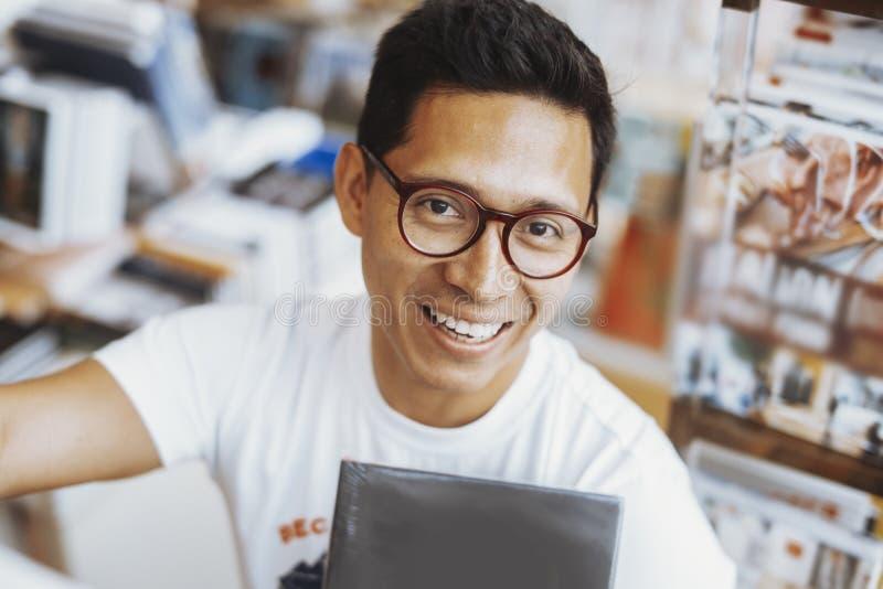 Homem de óculos novo que sorri e que guarda o livro nas mãos em umas livrarias fotos de stock royalty free