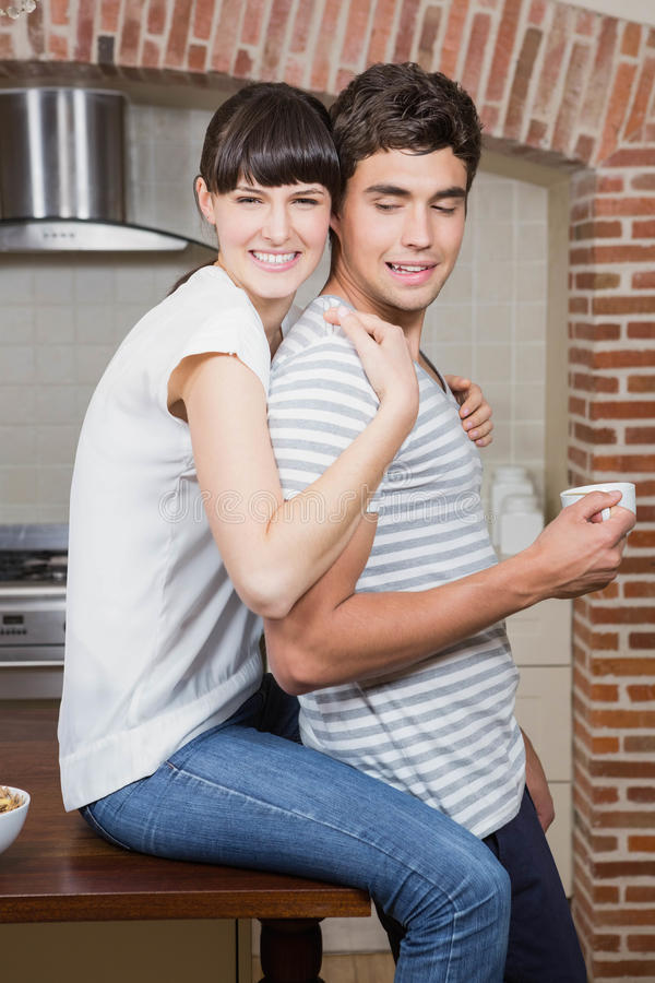 Homem de abraço da jovem mulher na cozinha fotografia de stock royalty free