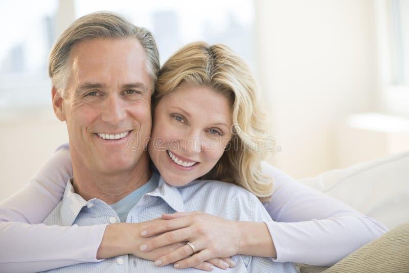 Homem de abraço da mulher loving de trás em casa imagem de stock