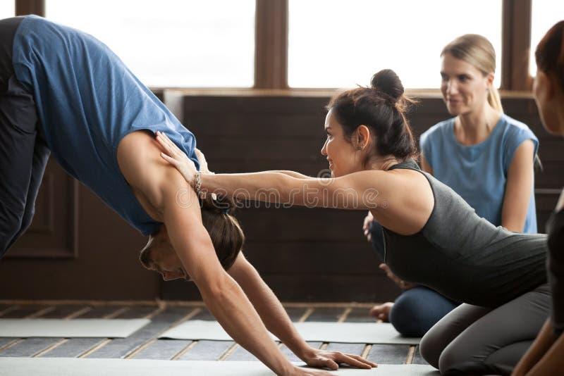 Homem de ajuda do professor da ioga para esticar guardar as mãos em ombros imagens de stock