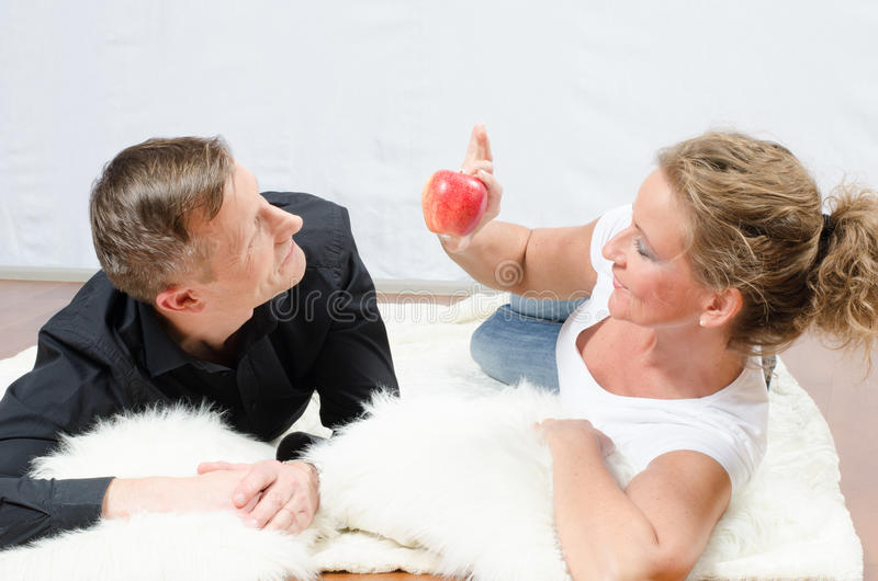 Homem de arrelia da mulher com maçã fotografia de stock royalty free