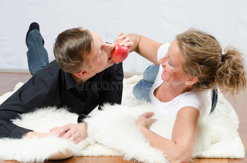 Homem de arrelia da mulher com maçã fotografia de stock