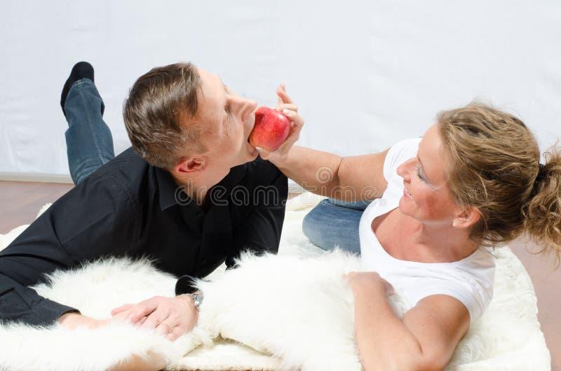 Homem de arrelia da mulher com maçã fotos de stock