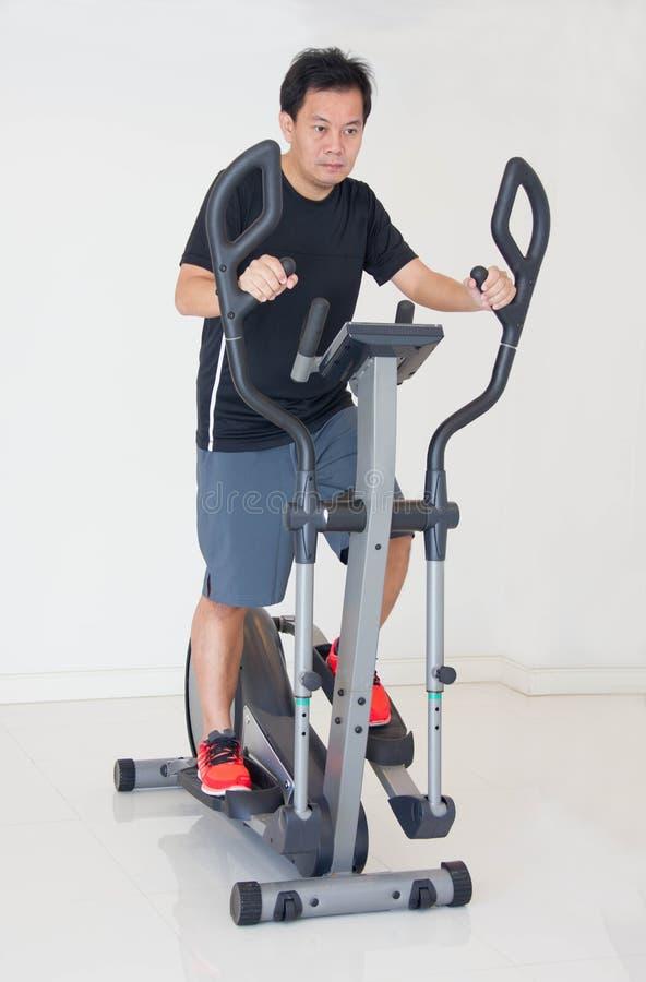 Homem de Asain que faz exercícios no instrutor transversal elíptico imagens de stock