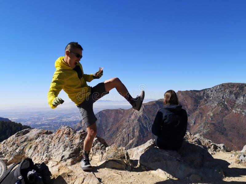 Homem de bicicleta asiático brincando com uma caminhadora caucasiana que está desfrutando da vista de Sardine Peak Trailhead fotografia de stock royalty free