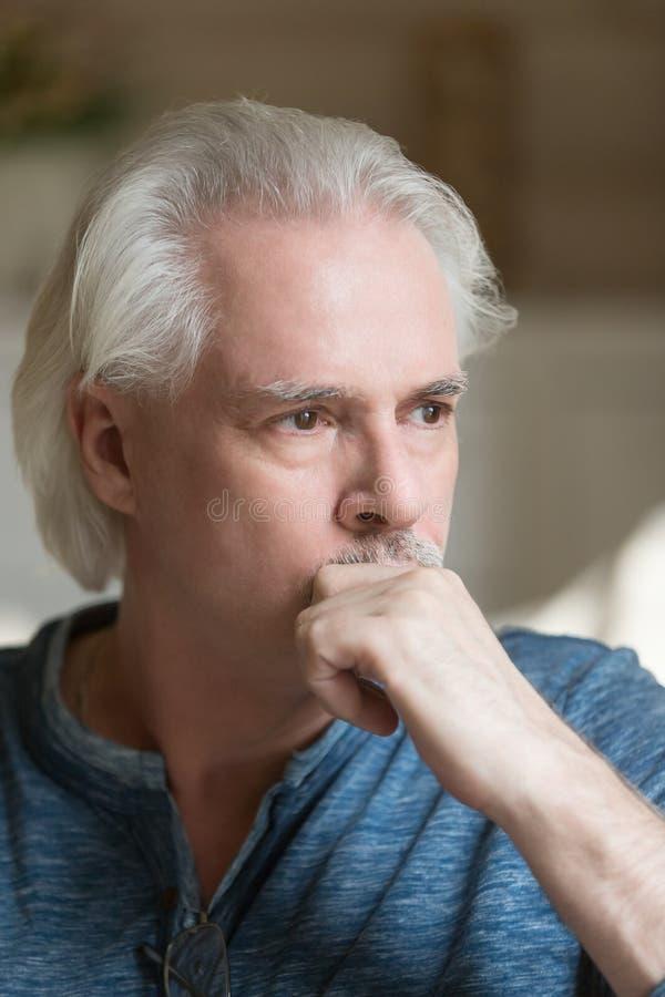 Homem de cabelo cinzento confundido focalizado em casa fotografia de stock