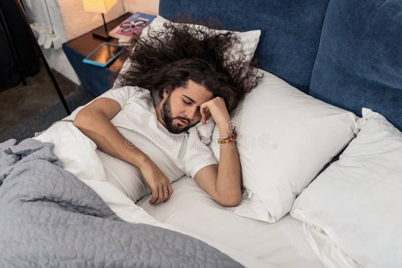 Homem de cabelos compridos agradável que tenta dormir fotos de stock