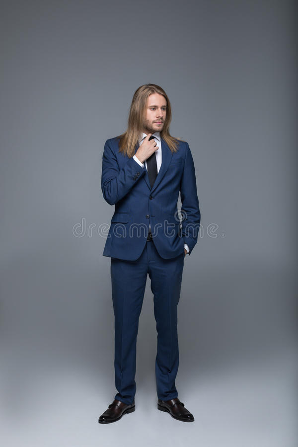 Homem de cabelos compridos considerável que veste o terno à moda e que olha afastado fotografia de stock royalty free