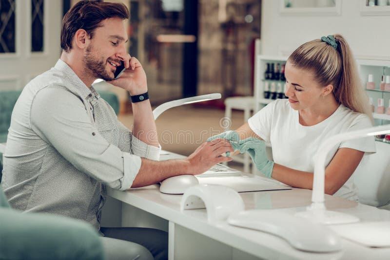 Homem de cabelos curtos atento que tem a conversação agradável durante a sessão do tratamento de mãos foto de stock