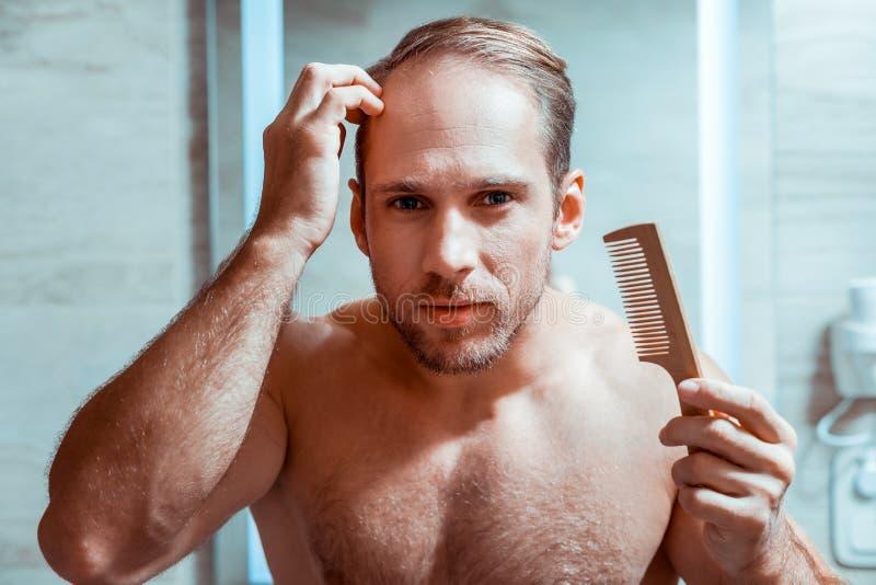 Homem de cabelos curtos diligente que corrige seu penteado com escova pequena fotos de stock royalty free