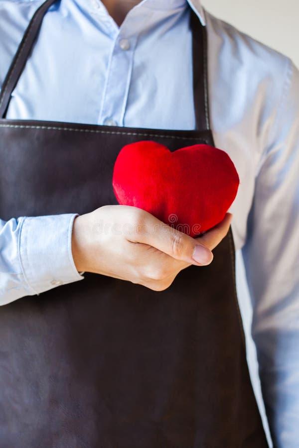 Homem de conservação no avental que guarda o coração - o relacionamento e o serviço do cliente ocuparam-se do conceito do negócio imagens de stock