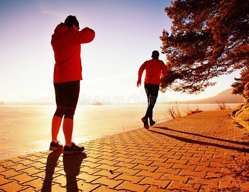 Homem de corrida do rel?gio da mulher Est?o treinando junto no rio fotografia de stock