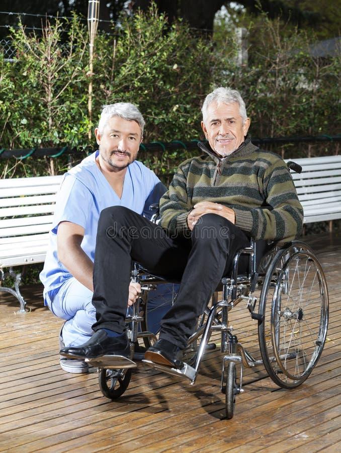 Homem de Crouching By Senior do fisioterapeuta na cadeira de rodas no gramado imagem de stock