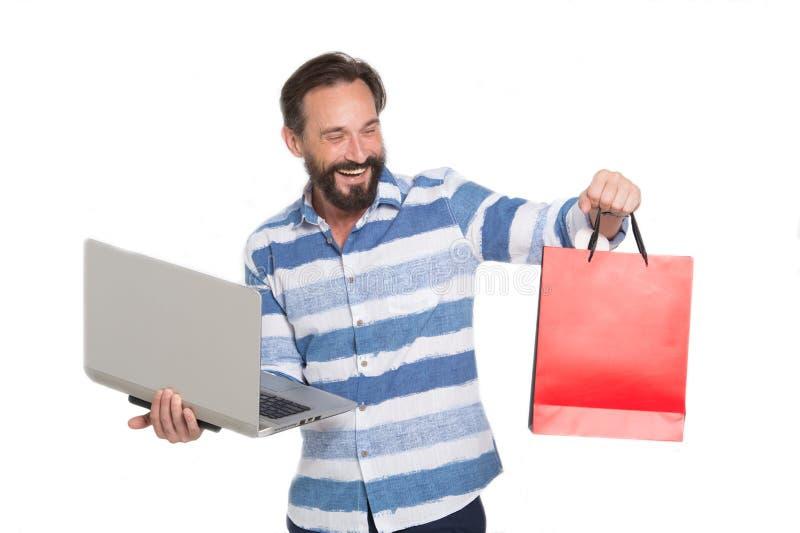 Homem de Delighter que olha o saco de papel ao guardar o dispositivo moderno imagens de stock