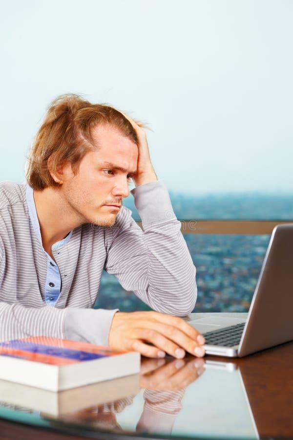 Homem de Depresssed na frente do portátil fotografia de stock