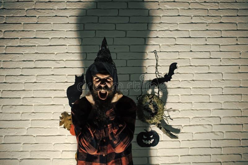 Homem de Dia das Bruxas no chapéu da bruxa que grita com medo imagens de stock