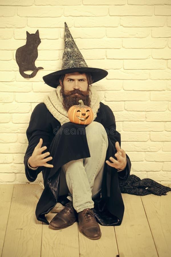 Homem de Dia das Bruxas no chapéu da bruxa que senta-se no assoalho imagens de stock royalty free