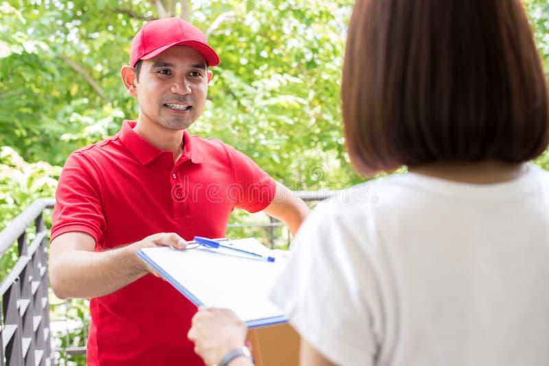 Homem de entrega asiático que dá a prancheta a uma mulher ao sinal fotos de stock