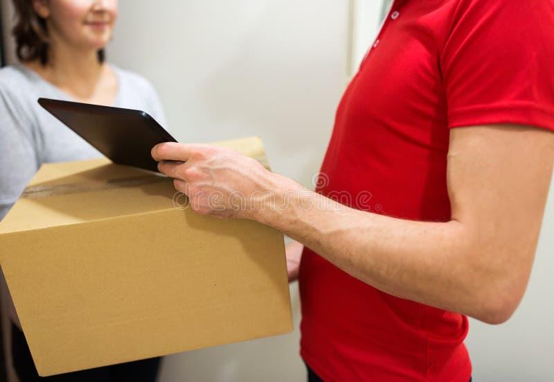 Homem de entrega com caixa, PC da tabuleta e cliente fotos de stock