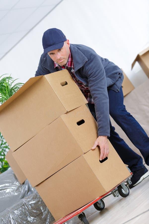 Homem de entrega com pacote do cardbox do lote imagem de stock