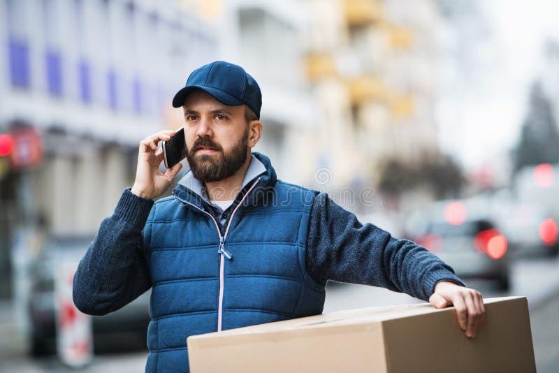 Homem de entrega com uma caixa do pacote na rua fotos de stock royalty free