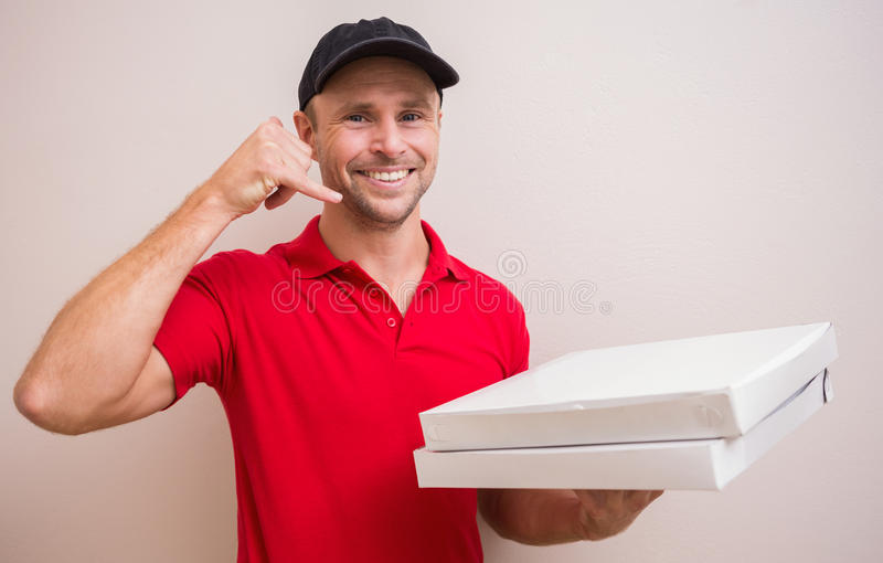 Homem de entrega da pizza que faz o gesto do telefonema fotografia de stock royalty free
