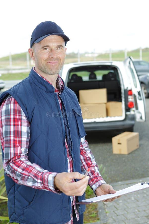 Homem de entrega de sorriso que guarda a caixa de cartão imagens de stock royalty free