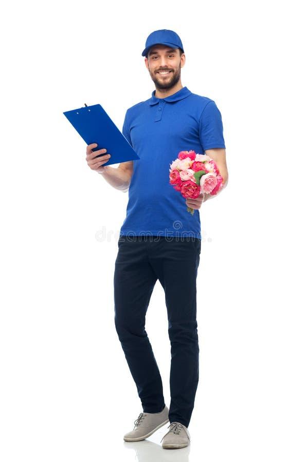 Homem de entrega feliz com flores e prancheta fotografia de stock royalty free