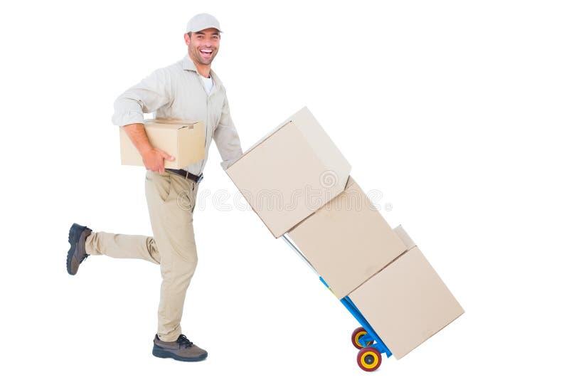 Homem de entrega feliz com o trole das caixas que correm no fundo branco fotografia de stock