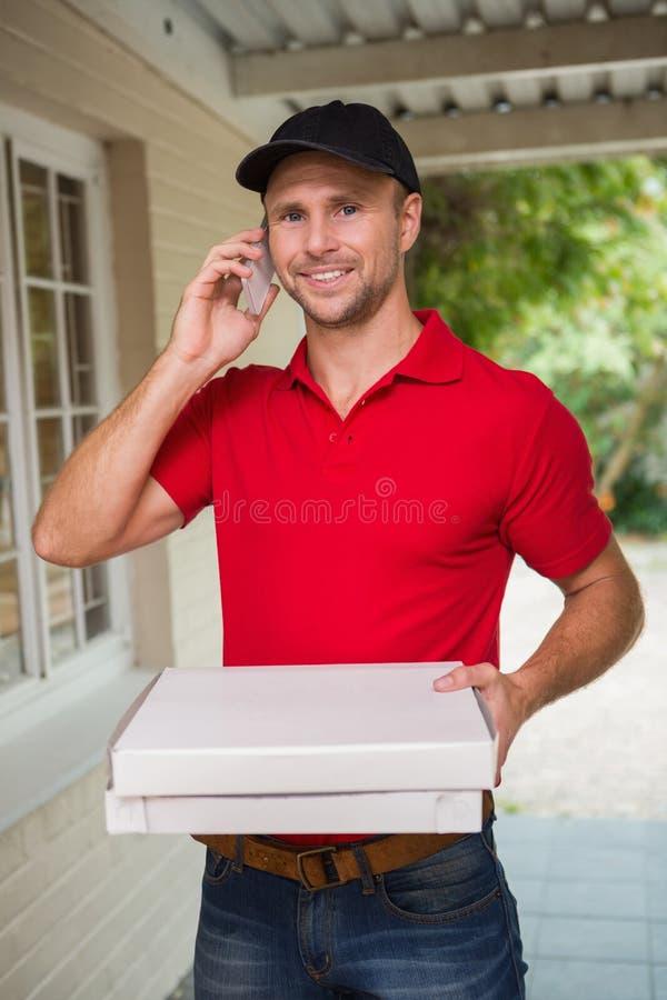 Homem de entrega feliz da pizza no telefone fotos de stock