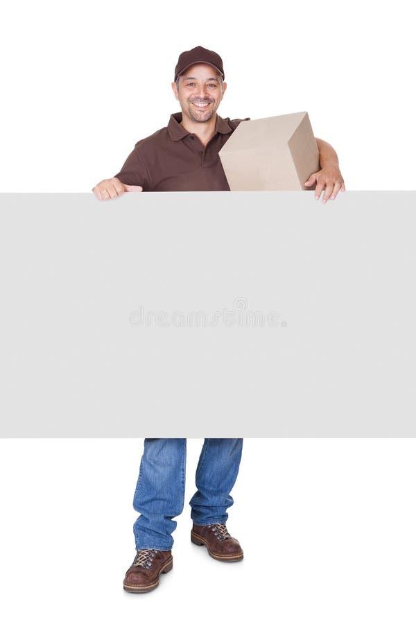 Homem de entrega feliz que guardara Cardbox e cartaz fotografia de stock royalty free