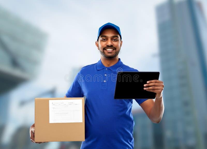 Homem de entrega indiano com PC da tabuleta e caixa do pacote fotos de stock