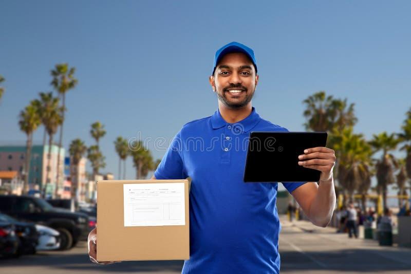 Homem de entrega indiano com PC da tabuleta e caixa do pacote imagem de stock