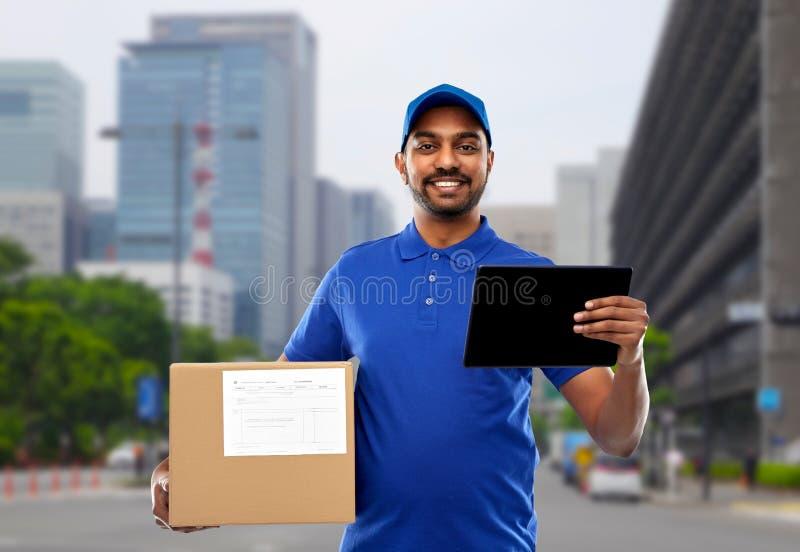Homem de entrega indiano com PC da tabuleta e caixa do pacote fotografia de stock