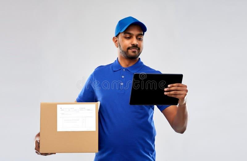 Homem de entrega indiano com PC da tabuleta e caixa do pacote imagens de stock